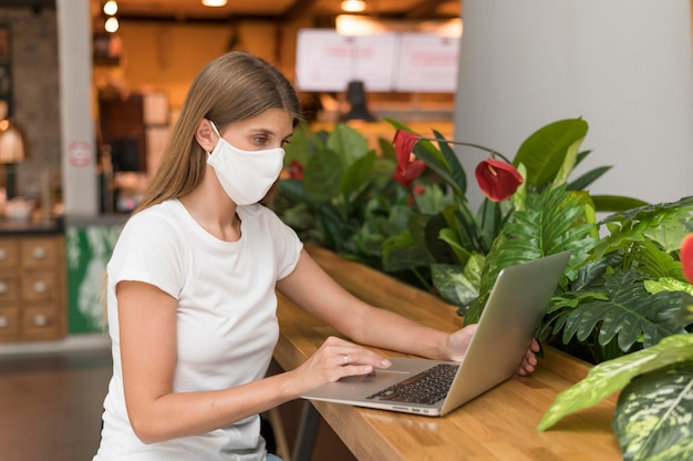 Woman working on laptop with mask