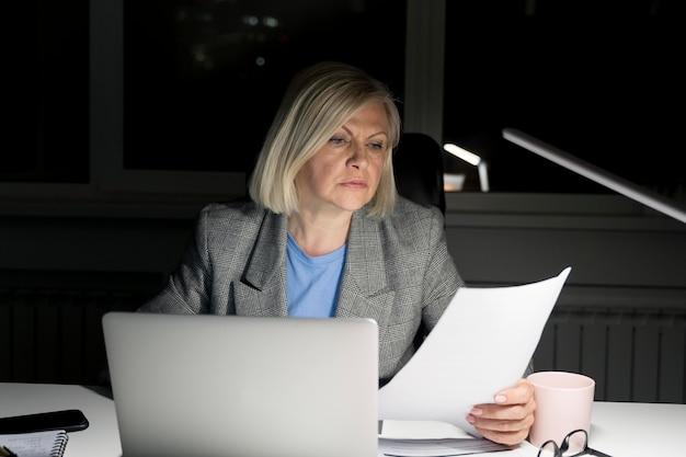 Женщина работает допоздна в офисе