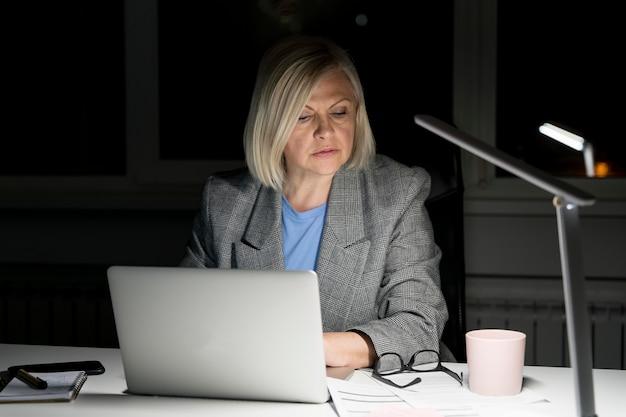 Donna che lavora fino a tardi in ufficio