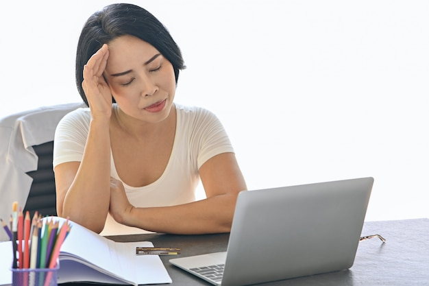 Woman working at office desk in front of laptop suffering from chronic daily headaches hand holding head concept for treatment online, appointment to a medical consultation