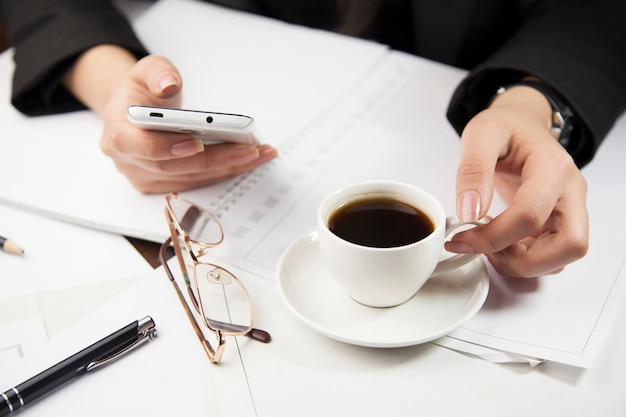 Woman working at office and drinking coffee