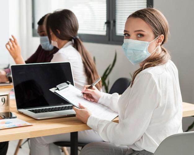 Donna che lavora in ufficio durante la pandemia con la maschera