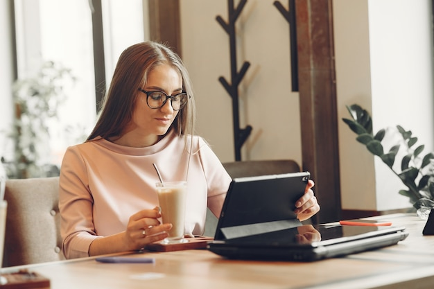 Woman working at the office. lady with a tablet. woman in a white blouse.