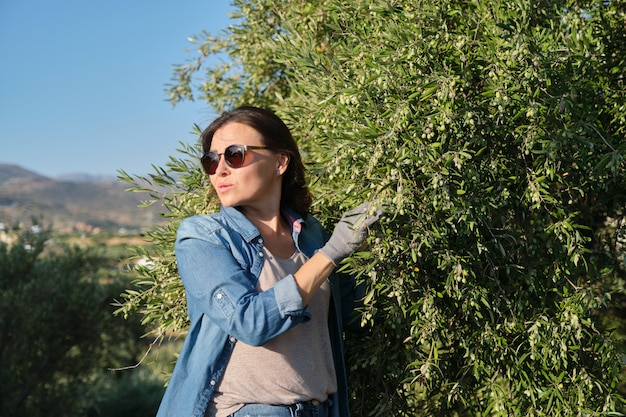 Woman working in the olive garden, mountain background