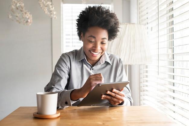 新しい通常のデジタルタブレットに取り組んでいる女性