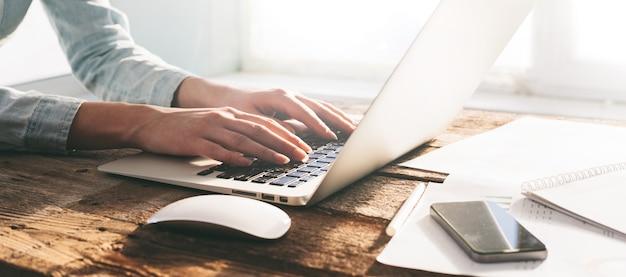 Женщина работает на ноутбуке и планшетном пк в помещении