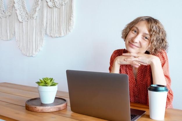 Женщина, работающая на ноутбуке в кафе.