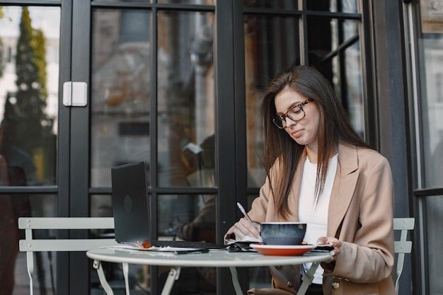 ストリートカフェでラップトップに取り組んでいる女性