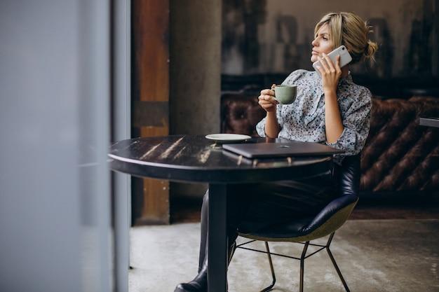 Женщина работает на компьютере и пьет кофе