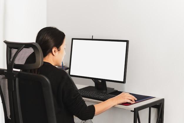Женщина работает на компьютере дома во время пандемии коромавируса.