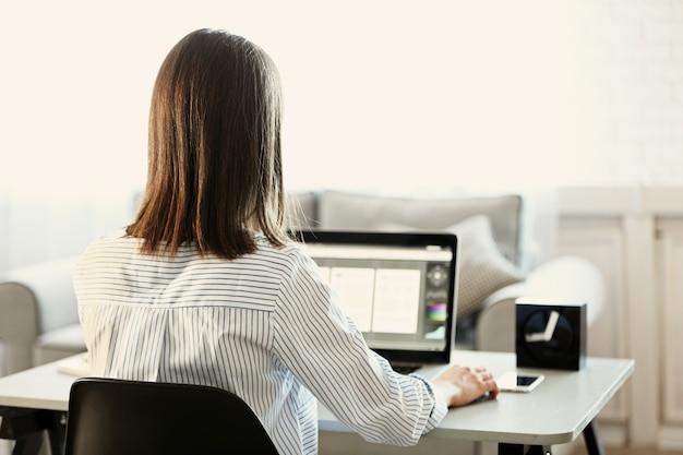 집에서 컴퓨터에서 작업하는 여자