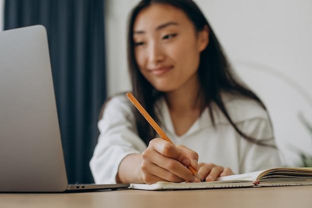 집에서 책상에서 컴퓨터 작업을 하는 여자
