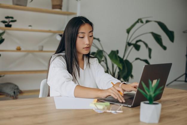 自宅の机でコンピューターに取り組んでいる女性