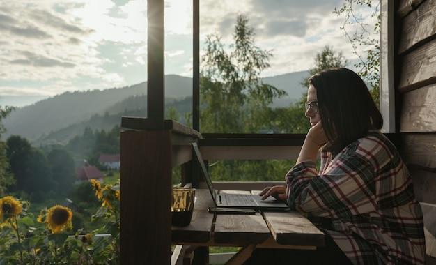 산의 전경을 조망할 수 있는 테라스에서 야외 컴퓨터 작업을 하는 여성