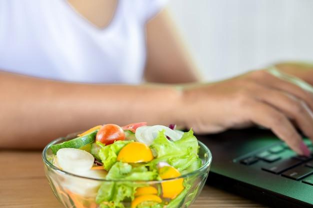 Женщина работает на компьютере с салатницей на столе
