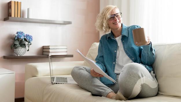 ソファで作業してコーヒーを飲む女性