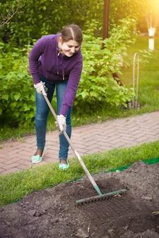 화창한 날에 정원 침대에서 작업하는 여자