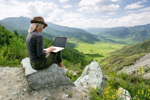 Женщина работает на своем компьютере на вершине горы.