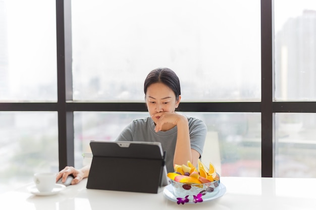 사무실에서 신선한 과일 한 그릇으로 그녀의 노트북에서 일하는 여자