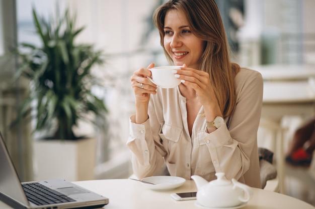 ラップトップで働いてお茶を飲む女性