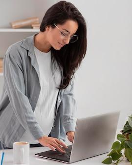 Женщина работает на ноутбуке дома во время беременности