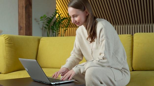 自宅で黄色いソファに座って、ラップトップコンピューターで作業している女性