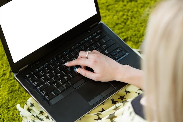 ラップトップに取り組んでいる女性。空の画面。キーボードでの入力