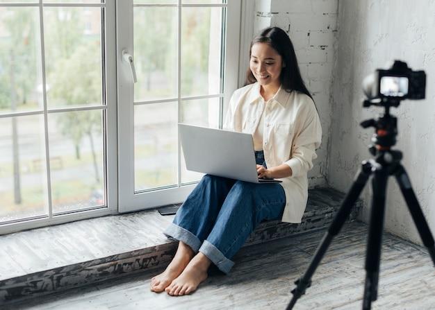 新しいvlogのためにラップトップに取り組んでいる女性