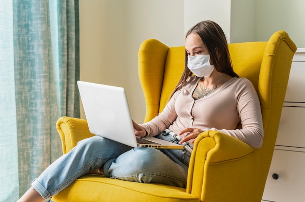 Женщина работает на ноутбуке из кресла во время пандемии в медицинской маске