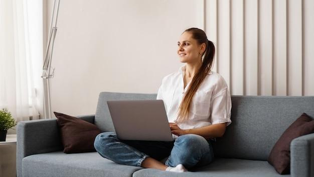 Женщина, работающая на ноутбуке из дома, или студент, обучающийся из дома, или фрилансер. современная бизнес-леди в белой рубашке и джинсах.