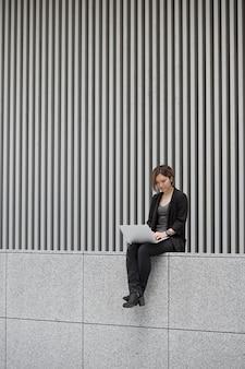 Женщина, работающая на ноутбуке полный выстрел