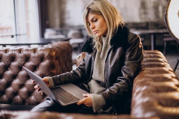 여자는 카페에서 노트북에서 일하고 코치 앉아