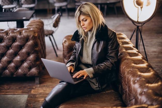 カフェでラップトップで作業し、コーチに座っている女性