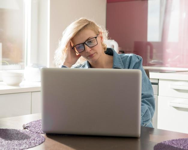 Женщина работает на ноутбуке в кухне
