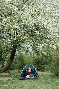 Женщина, работающая на ноутбуке в палатке на природе. молодой фрилансер сидит в лагере. отдых в кемпинге в лесу, на лугу. удаленная работа, активный отдых летом. счастливая девушка расслабляющий, работа в отпуске.