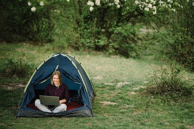 자연 속에서 텐트에 노트북에서 일하는 여자. 캠프에 앉아 젊은 프리랜서. 숲, 초원에서 캠핑 사이트에서 휴식. 원격 근무, 여름철 야외 활동. 행복 한 여자 휴식, 휴가 작업.