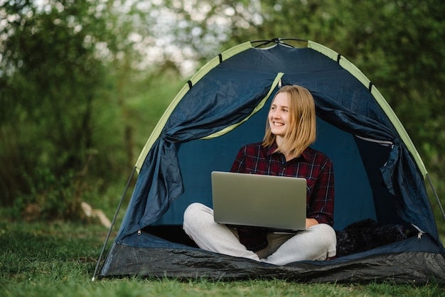 自然の中でテントの中でラップトップに取り組んでいる女性