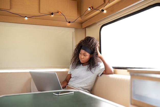 Женщина, работающая над средним выстрелом ноутбука