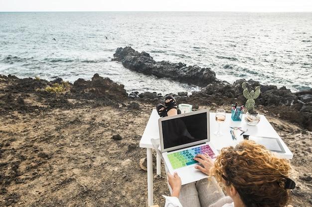 海の前のテーブルデスクに足を乗せて海岸に座っている間、カラフルなキーボードでラップトップに取り組んでいる女性。美しい海の前でラップトップに取り組んでいる実業家