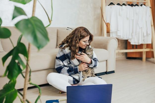 그녀의 고양이 함께 노트북에서 일하는 여자