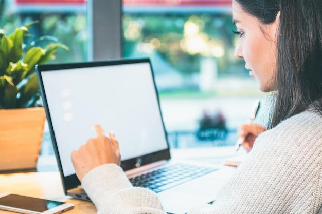 Женщина работает на ноутбуке с белым экраном, держа ручку
