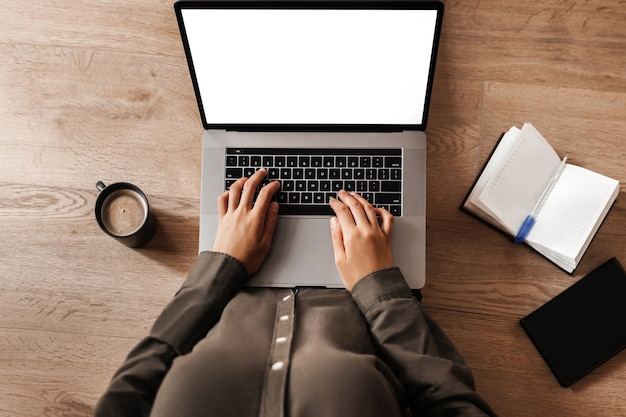 Женщина работает на ноутбуке с белым экраном, сидя на полу, вид сверху