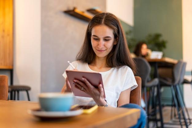 Женщина, работающая на планшете среднего кадра