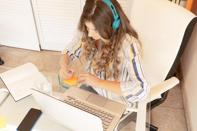Женщина работает или учится из дома, занятая женщина в наушниках, использующая современный портативный компьютер, пандемия коронавируса, работающая дома, стиль жизни
