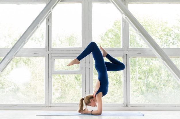 Woman working out against vintage window, doing yoga or pilates exercise