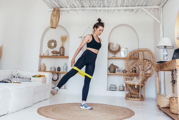 ゴムバンドを使って自宅で運動する女性。