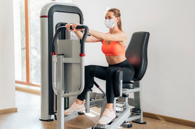 Женщина работает в тренажерном зале с маской
