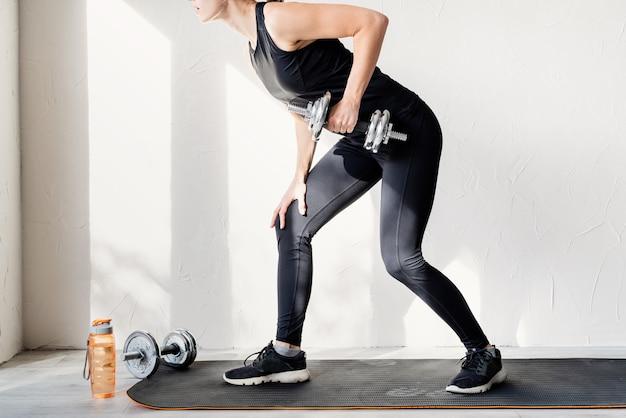 ダンベルリフトをしている女性が背中と腕をトレーニングしている