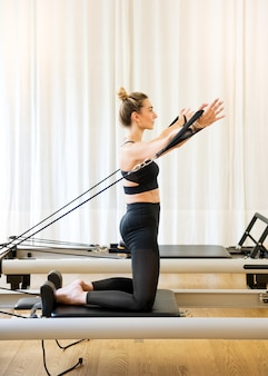 Woman working out doing pilates arm exercises