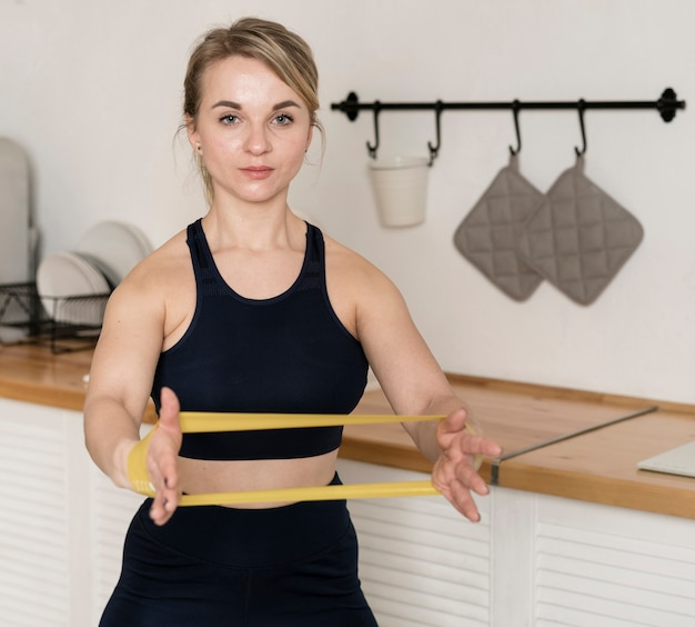 Woman working out at home with elastic bands